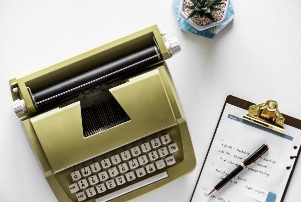 Máquina de escribir y carpeta en un escritorio.